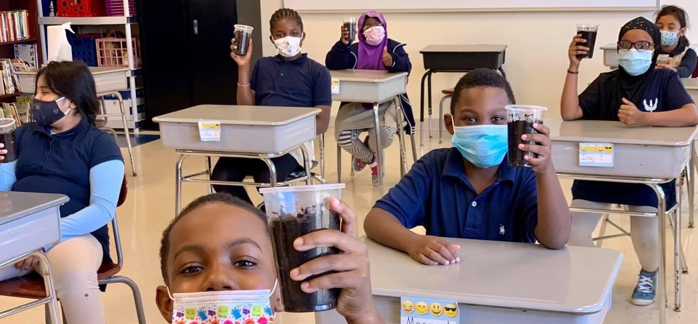 Students holding up planted seeds in cups in a classroom.