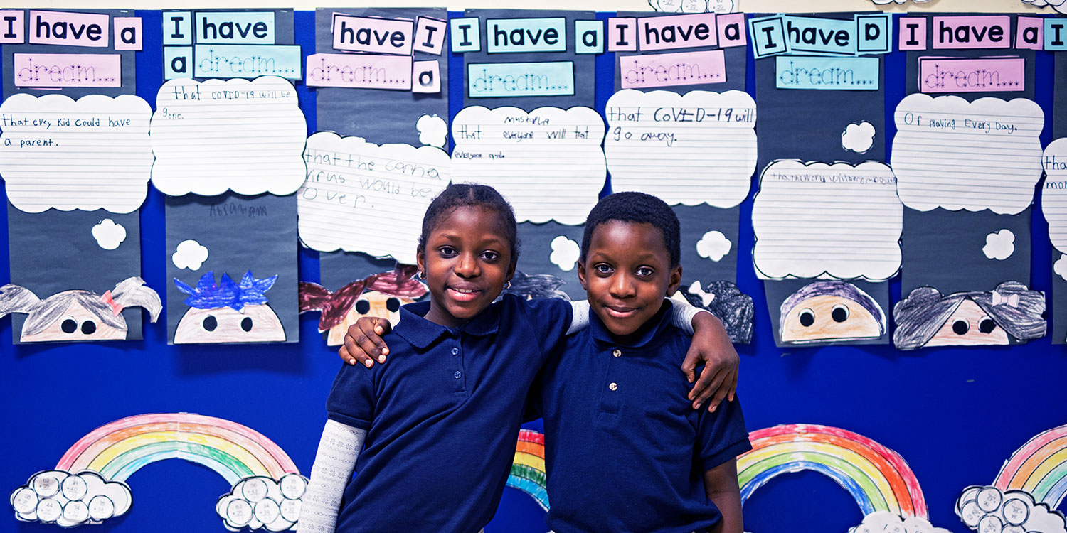 Elementary students smiling in front of bulletin board.