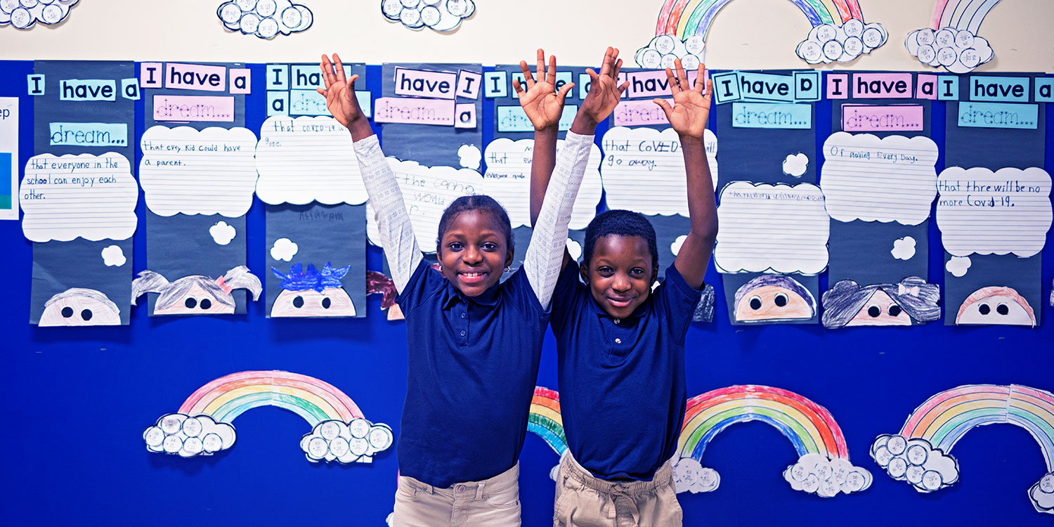Elementary students smiling and putting arms up in the air in front of bulletin board.